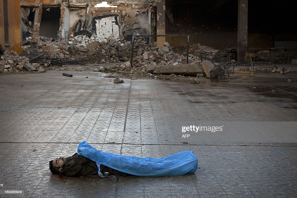 The body of a Syrian civilian, executed and dumped in the Quweiq river, lays in the grounds of the courtyard of a Yarmouk School, in the Bustan al-Qasr district of Aleppo, on January 29, 2013. The bodies of at least 65 young men, all executed with a single gunshot to the head or neck, were found in a river in Aleppo city, adding to the grim list of massacres committed during Syria's 22-month conflict.