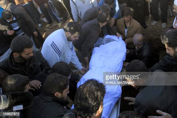 The body of a Syrian refugee who was killed the day before during an explosion is buried during his funeral in the northern city of Ramtha which...