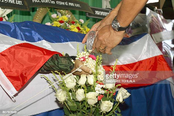 The body of a Thai soldier lays under a Thai flag as a colleague pours water giving the soldier his ''last bath'' at a temple in Narathiwat on April...