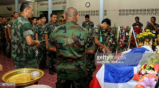 The body of a Thai soldier lays under a Thai flag as a colleague pour water giving the soldier his ''last bath'' at a temple in Narathiwat on April...