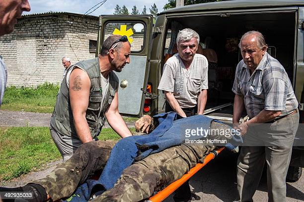 The body of a Ukrainian soldier killed during an attack on a military checkpoint earlier in the day by unknown forces is carried into the morgue on...