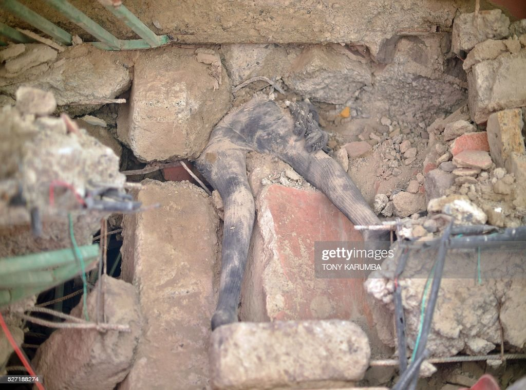 The body of a female lies trapped between collapsed slabs of concrete as rescuers search for bodies trapped in rubble on May 2, 2016 at the scene of a collapsed residential building in the low-income suburb of Huruma in Nairobi. The death toll in the collapse of a six-storey building in Nairobi on April 29 rose to 21 on May 2 after four more bodies were pulled from the rubble of the residential structure that gave way during weekend storms. / AFP / TONY