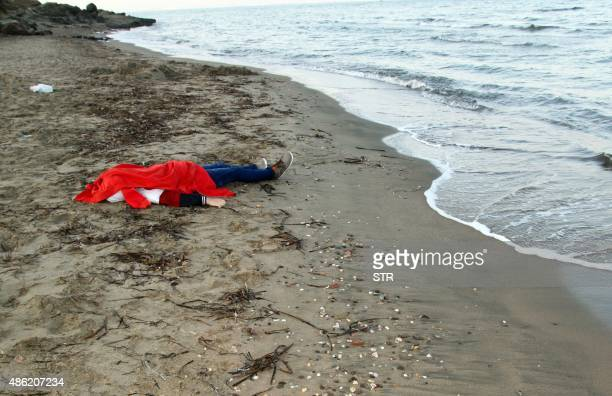 The body of a young man is covered as it lies on the shores of the city of Bodrum in southern Turkey after a boat carrying refugees sank as it...