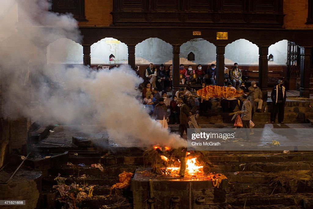 The body of an earthquake victim is carried past a cremation ceremony at Pashupatinah Temple on April 29 2015 in Kathmandu Nepal A major 78...