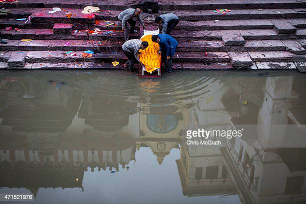 The body of an earthquake victim is washed ahead of a cremation ceremony at Pashupatinah Temple on April 29 2015 in Kathmandu Nepal A major 78...