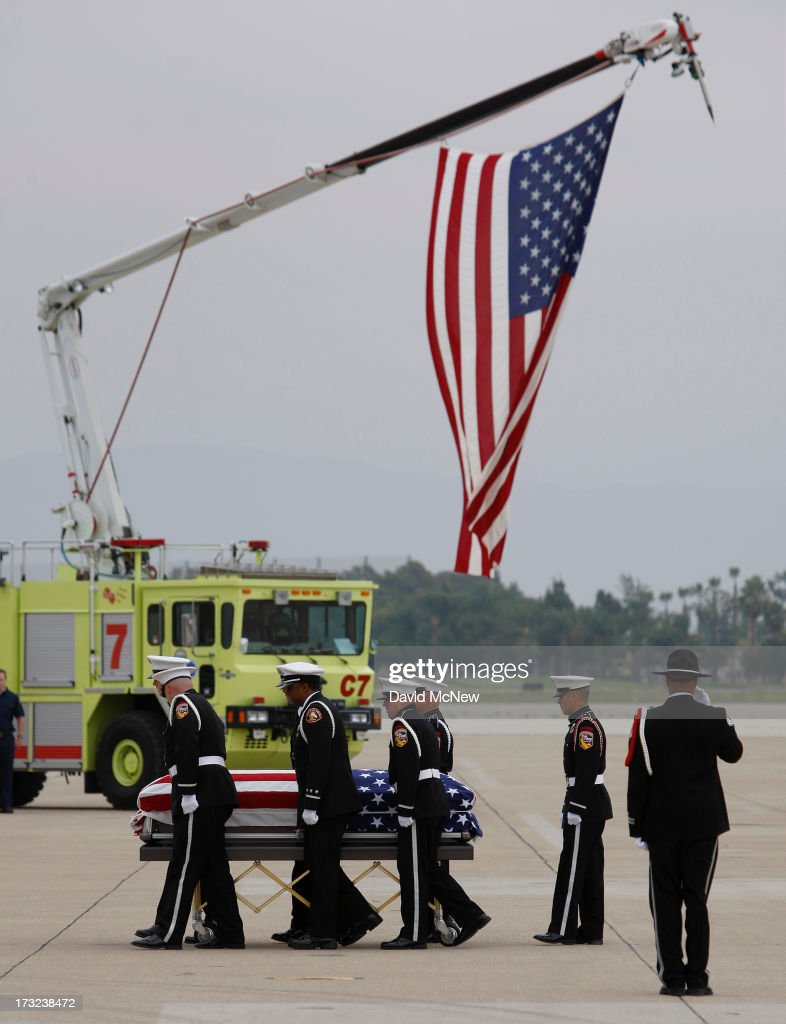 The body of Christopher MacKenzie is carried from a C-130 transport plane as two of the nineteen firefighters killed fighting the Yarnell Fire in Arizona arrive to the Joint Forces Training Base, Los Alamitos Air Field on July 10, 2013 in Los Alamitos, California. The memorial ramp ceremony, coordinated in part by the California Fire Foundations Last Alarm Service Team, honors Granite Mountain Interagency Hotshot Crew members 21-year-old Kevin Woyjeck and 20-year-old Christopher MacKenzie.