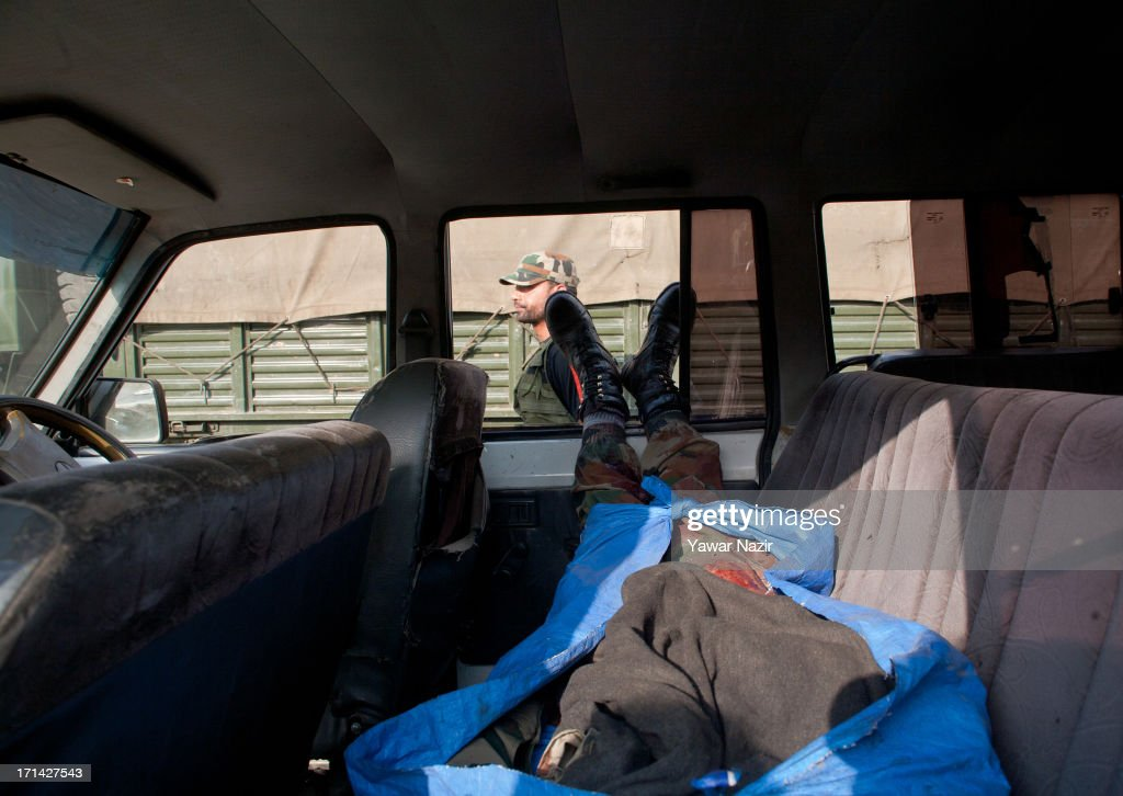 The body of Indian army soldier lies in a vehicle after militants attacked their convoy on June 24, 2013 in Srinagar, the summer capital of Indian administered Kashmir, India. Suspected militants opened fire on an Indian army convoy on the outskirts of Srinagar, killing at least five and wounding seven others, ahead of Indian Prime Minister Manmohan Singh's visit to the disputed Himalayan region tomorrow. The militants fled from the scene and half an hour later hurled a grenade on Indian paramilitary forces in Barzulla area , some two kilometers away. Hizbul-Mujahideen, the largest guerrilla group fighting Indian rule since 1989, claimed responsibility for today's attack, and had just two days before gunned down two policemen in the heart of Srinagar city.