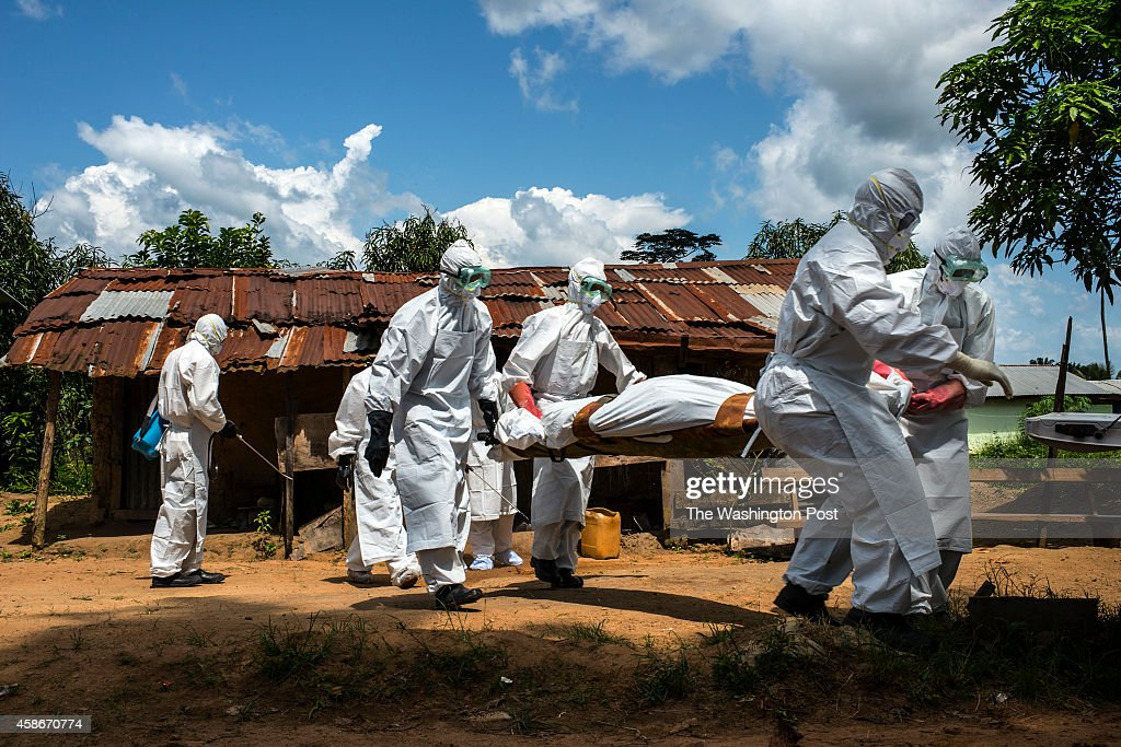 The body of Jacqueline Morris is carried to the back of a pickup truck by a county health burial team on Friday November 7 2014 in Voinjama Liberia...