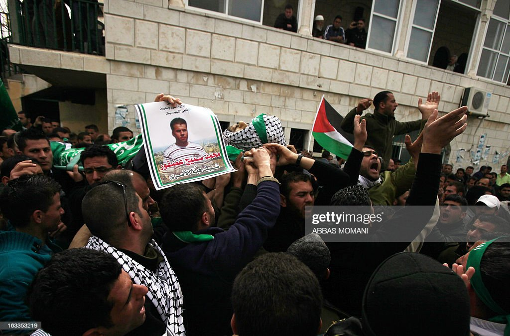 The body of Mohammad Asfour is carried during his funeral in the West Bank village of Abud on March 8, 2013. Asfour, a 22-year-old student studying sports, died of his wounds on March 7 as he was wounded in the head by a rubber-coated steel bullet fired by Israeli troops during a protest which erupted after a prisoner died in Israeli custody.