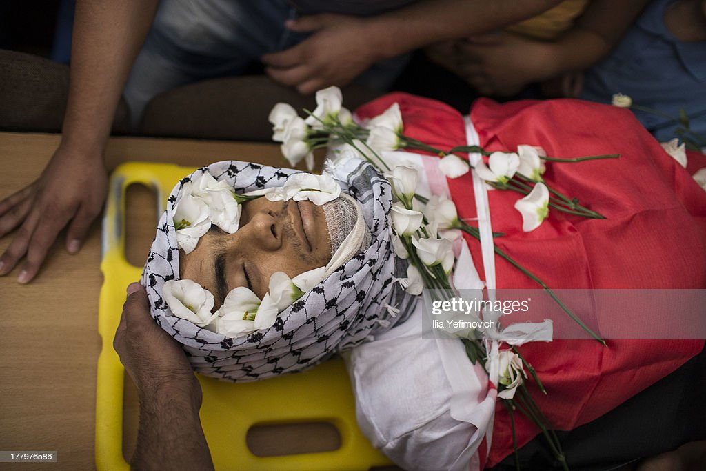 The body of one dead Palestinian is seen during the funeral held for three Palestinians killed during IDF operation at Kalandia refugee camp on August 26, 2013 in Ramallah, West Bank. At least 15 people were injured as Palestinians clash with undercover Israeli troops.