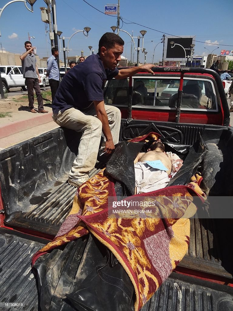 The body of one of the victims killed in yesterday's bombings in Hawijah north of Baghdad is transported in the back of a truck to be handed over to his family for burial in the northern Iraqi city of Kirkuk on April 24, 2013. A wave of clashes and attacks involving Iraqi security forces, protesters and their supporters on April 23, left 54 people dead and prompted two Sunni ministers to quit, sending tensions soaring.