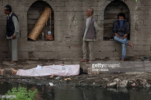 The body of one of the victims of the earthquake that hit Nepal yesterday lays on the ground before cremation while relatives sit near by on April 26...