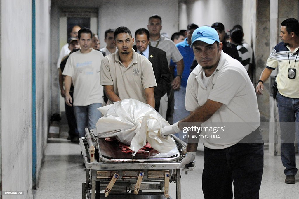 The body of Orlan Chavez, Fiscal Unit Against Money Laundering, who was killed by gunmen, is carried on stretcher in Tegucigalpa on April 18, 2013. The homicide rate in Honduras is the highest in the world, with 85.5 murders per 100,000 inhabitants, despite the 'security policy' implemented by the government of President Porfirio Lobo. AFP PHOTO / Orlando SIERRA.