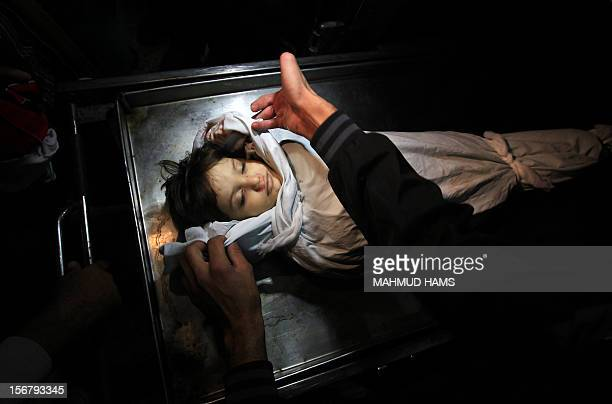 The body of Palestinian boy Abdel Rahman Majdi Naim lies in a hospital morgue after he was killed in a second Israeli strike on the building housing...