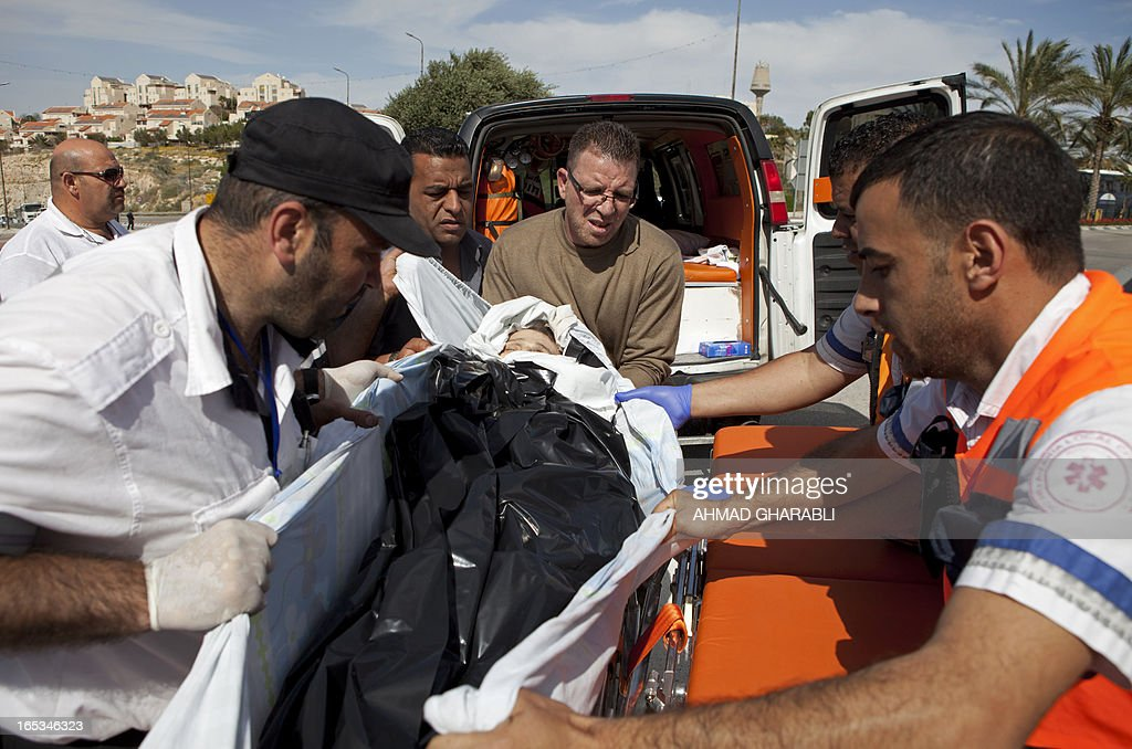 The body of the Palestinian prisoner Maisara Abu Hamdiyeh is handed over by Israeli authorities to the members of the Palestinian Red Crescent near to the entrance of the largest Jewish settlement of Maale Adumin, on the outskirts of Jerusalem, on April 3, 2013. Hamdiyeh, who had served 10 years of a life sentence for attempted murder, died in an Israeli hospital the previous morning two months after being diagnosed with throat cancer.