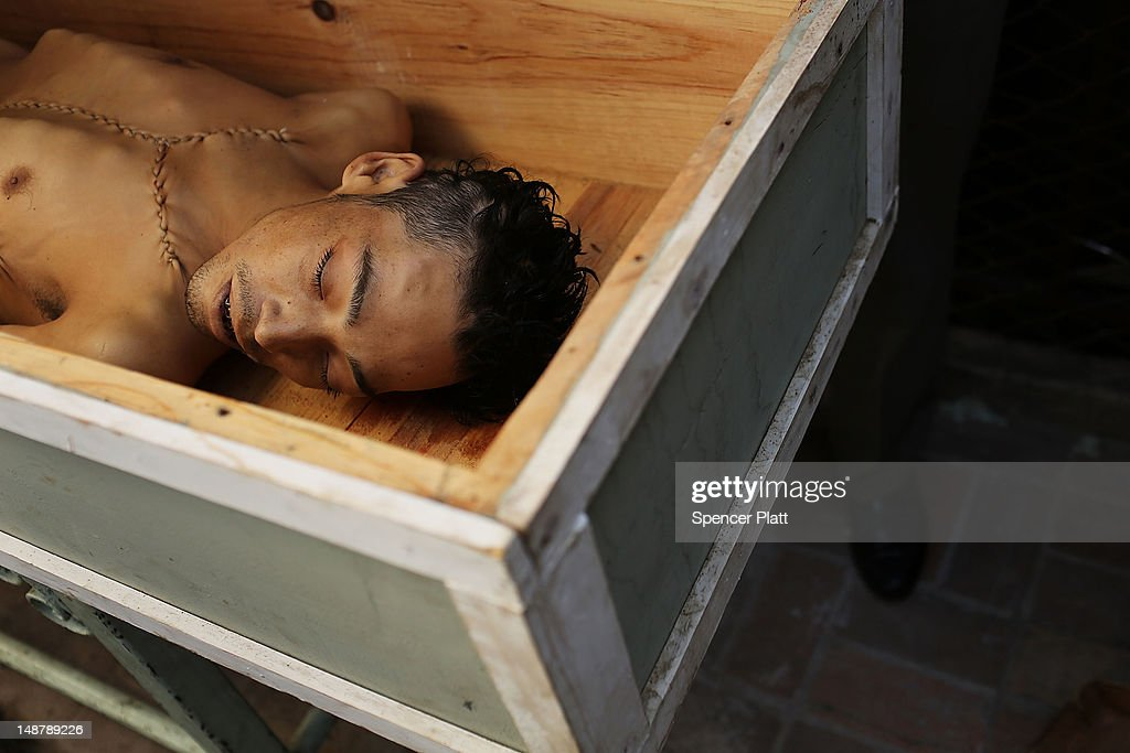 The body of Walter Lopez, 24, is viewed in a funeral parlor after he was recently killed during a fight in a pool hall on July 19, 2012 in Tegucigalpa, Honduras. Honduras now has the highest per capita murder rate in the world and its capital city, Tegucigalpa, is plagued by violence, poverty, homelessness and sexual assaults. With an estimated 80% of the cocaine entering the United States now being trans-shipped through Honduras, the violence on the streets is a spillover from the ramped rise in narco-trafficking.