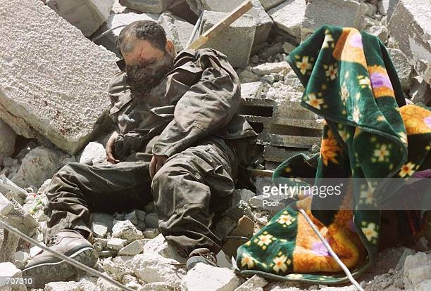 The body of what Israeli forces claim is a Palestinian fighter lays sprawled amidst the rubble of houses April 14 2002 in the northeast tip of the...