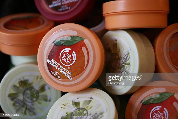 The Body Shop logo sits on the lids of body butter moisturiser inside a Body Shop International Plc store owned by L'Oreal SA in London UK on...