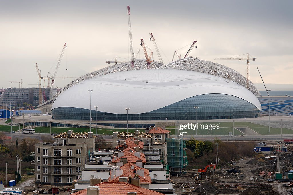 The Bolshoy Ice Dome is seen beyond the partially-completed buildings of the athletes village in the Sochi district of Adler, on February 18, 2013. With a year to go until the Sochi 2014 Winter Games, construction work and development continues as Olympic tests events and World Championship competitions are underway. AFP PHOTO / LEON NEAL