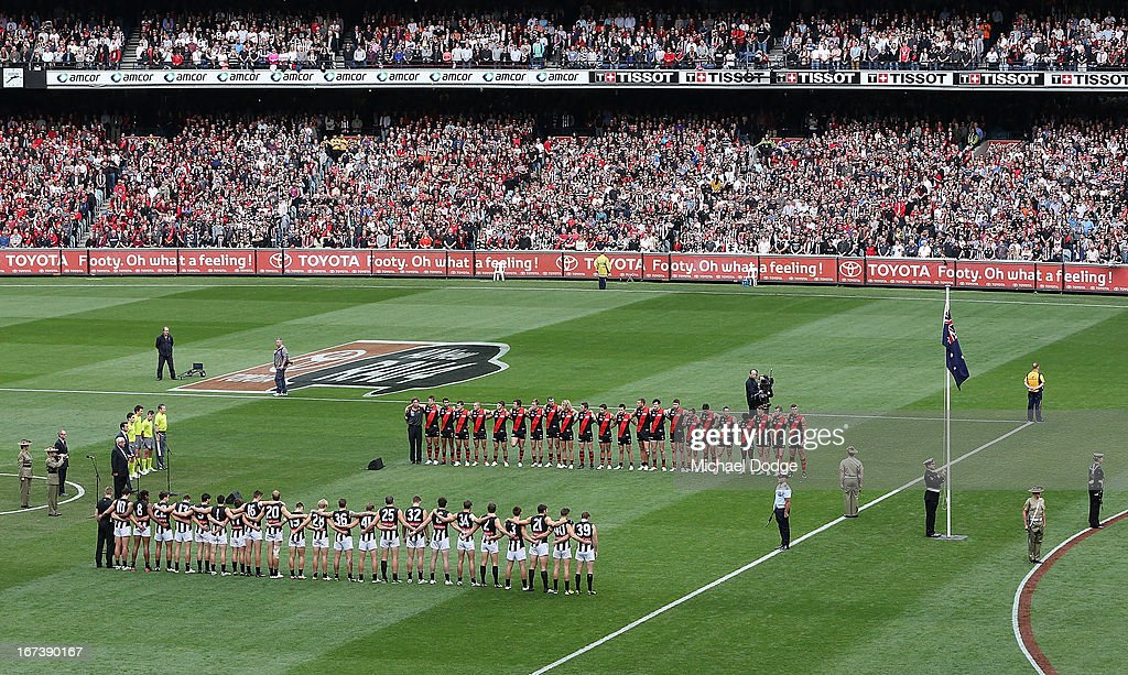 The Bombers and Magpies players stand for a minutes silence in tribute to the Anzacs during the round five AFL match between the Essendon Bombers and the Collingwood Magpies at Melbourne Cricket Ground on April 25, 2013 in Melbourne, Australia.