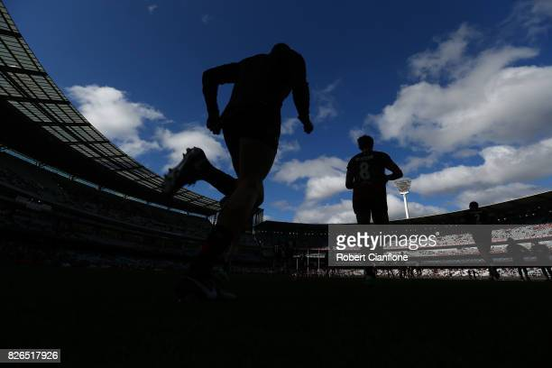 The Bombers run out for the warm up session prior to the round 20 AFL match between the Essendon Bombers and the Carlton Blues at Melbourne Cricket...