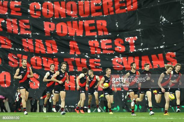 The Bombers run through the banner during the round 14 AFL match between the Sydney Swans and the Essendon Bombers at Sydney Cricket Ground on June...