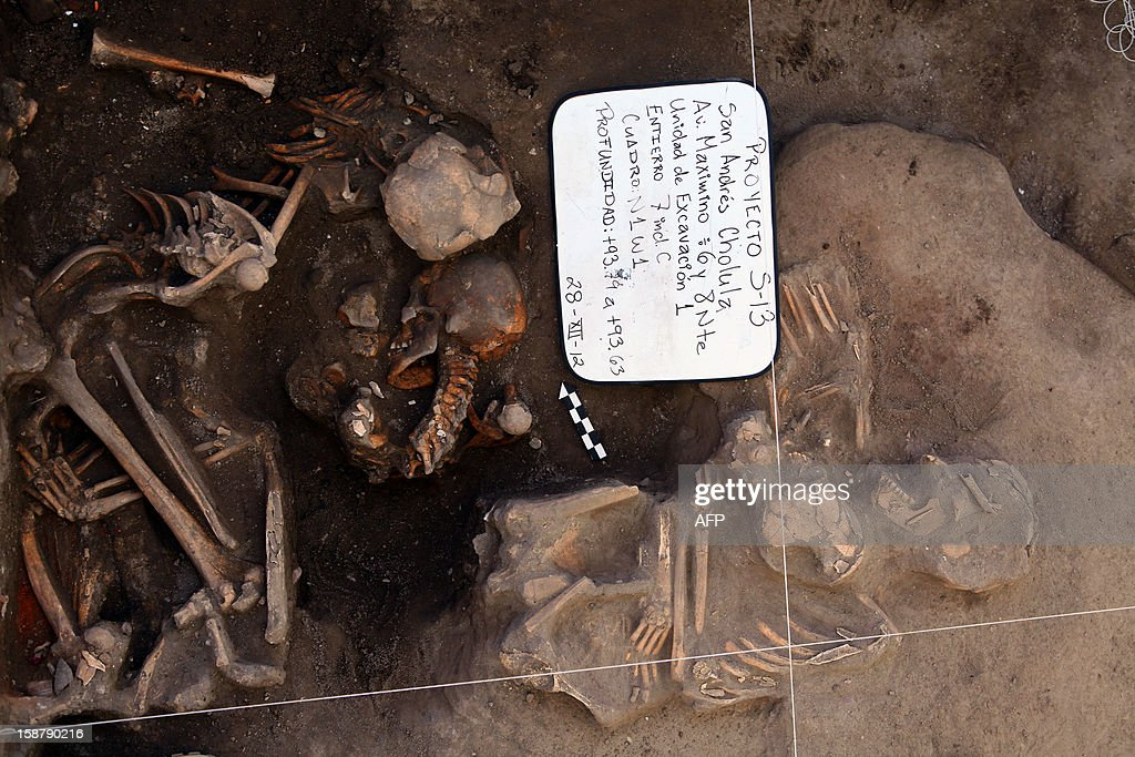 The bones of bodies are seen at an excavation site December 28, 2012 in Cholula, a town 120 kilometers north of the Mexican capital. Archeologists in central Mexico uncovered the bones of 12 children and adults who may have been buried 800 years ago, a National Institute of Anthropology and History expert told AFP. The skeletons were discovered as the archeologists supervised the installation of a new drain in an old neighborhood of Cholula. AFP PHOTO/Jose Castanares