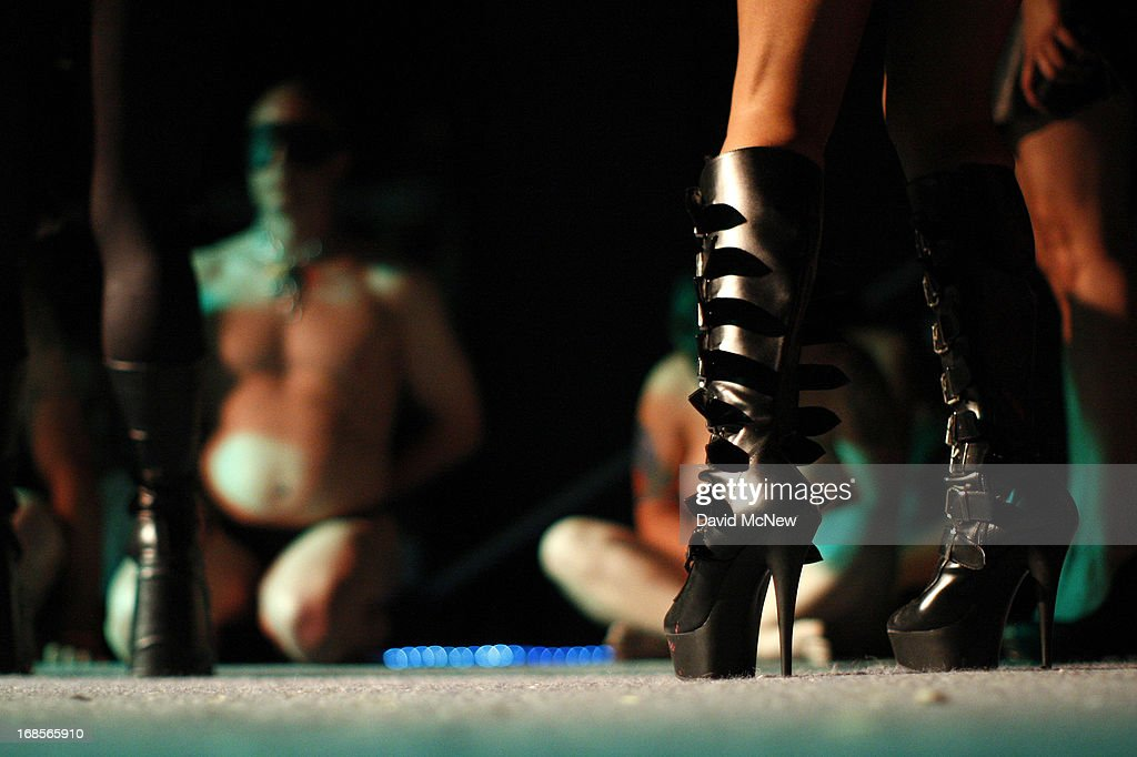 The boots of a dominatrix are seen as men and woman in a contest to be the best submissive kneel at a dungeon party during the domination convention, DomConLA, in the early morning hours of May 11, 2013 in Los Angeles, California. The annual convention was started in 2003 by fetish professional Mistress Cyan to bring together enthusiasts of BDSM (Bondage, Discipline, Dominance/Submission, and Sadomasochism) and other fetishes.