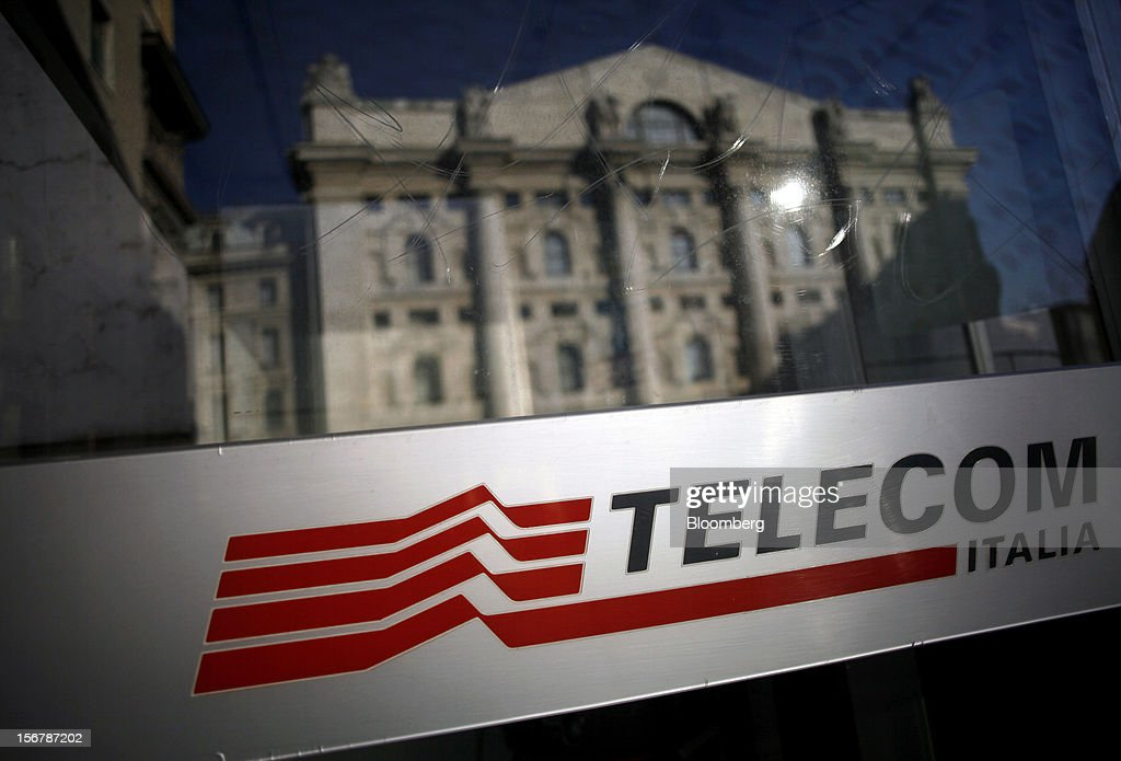 The Borsa Italiana, Italy's stock exchange, is reflected on the glass of a public telephone booth operated by Telecom Italia SpA, in Milan, Italy, on Tuesday, Nov. 20, 2012. Telecom Italia SpA said it is still reviewing the possible spinoff of its fixed-line network and the company's board will discuss the outcome of its analysis on Dec. 6. Photographer: Alessia Pierdomenico/Bloomberg via Getty Images