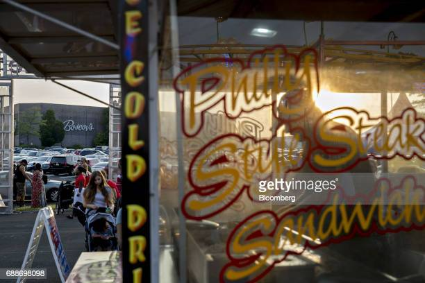 The Boscov's Department Store LLC stands past a concession stand during the Dreamland Amusements carnival in the parking lot of the Neshaminy Mall in...