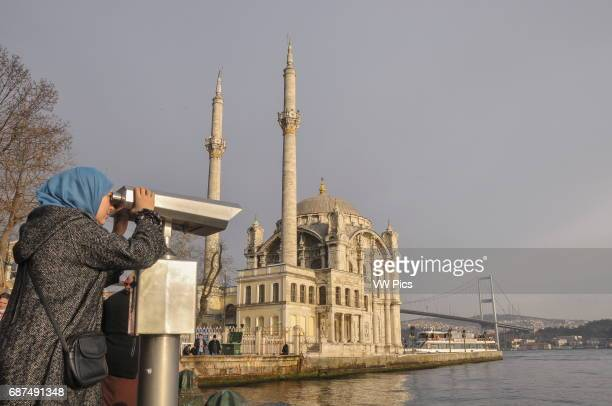 The Bosphorus seafront at Ortak_y on the European side of Istanbul A young Turkish woman watches the Asian bank of the Bosphorus with a pair of...