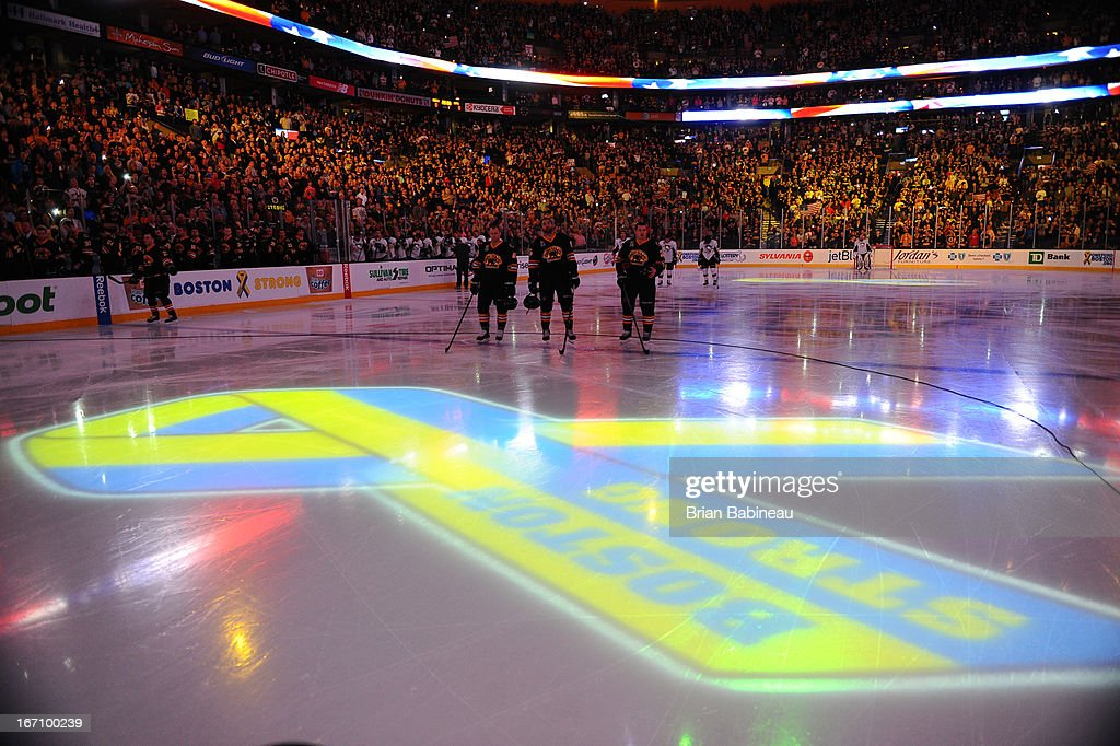 The Boston Bruins stand on the ice in front of a ribbon projected that says Boston Strong durng the national anthem prior to the game against the Pittsburgh Penguins at the TD Garden on April 20, 2013 in Boston, Massachusetts.