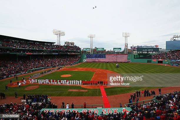 The Boston Red Sox and the Baltimore Orioles stand for the national anthem before the Red Sox home opener at Fenway Park on April 11 2016 in Boston...