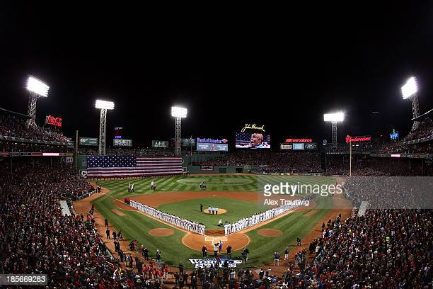 The Boston Red Sox and the St Louis Cardinals on the field for the natoinal anthem before the start of Game One of the 2013 World Series at Fenway...