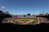 The Boston Red Sox and the Washington Nationals stand on the field for the National Anthem before the game at Fenway Park on April 13 2015 in Boston...