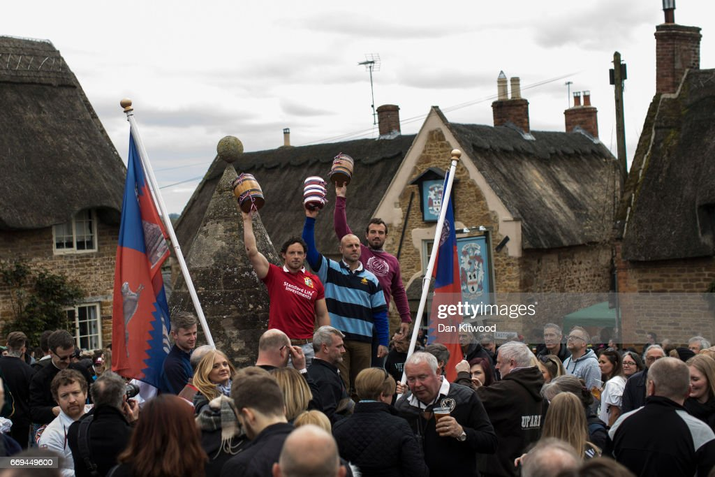 The Bottles are held aloft by members of the Hallaton team ahead of the bottle kicking on April 17, 2017 in Hallaton, England. Hallaton hosts the Hare Pie Scramble and Bottle Kicking event today. The Bottle Kicking follows the Hare Pie Scramble, two events that are combined to form an ancient custom that dates back to the early eighteenth century, and one of the oldest in British History. The first part consists of a blessing of a Hare Pie by a local vicar, before it is cut up and thrown to the crowd, who 'scramble' to get a piece, believing it will bring good luck. The second part, the Bottle kicking sees two rival villages, Hallaton, and neighboring Medbourne attempt to carry a 'bottle' which is actually a keg of beer, from the Hare Pie Bank, and get it across a boundary stream for their own village. The best of three contest can last several hours.