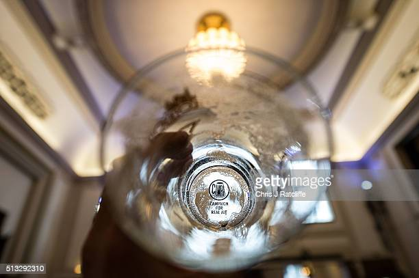 The bottom of a pint glass after beer has been drunk from it with the CAMRA logo on the bottom at the London Drinker Beer and Cider Festival at the...