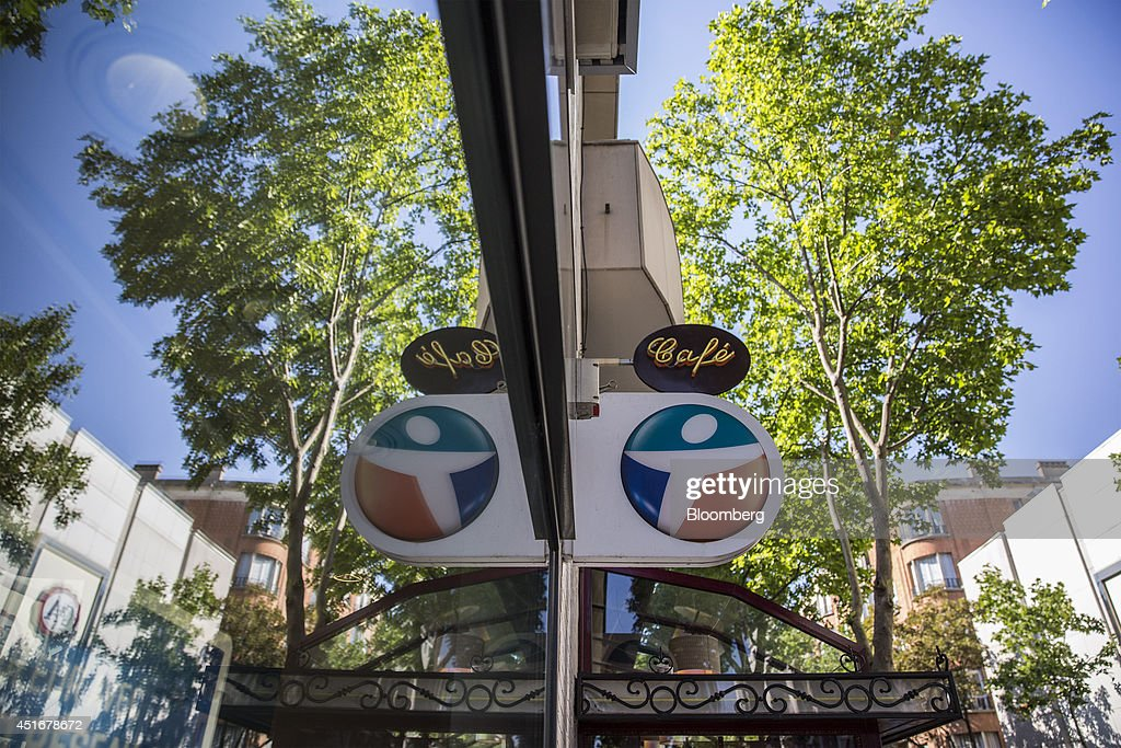The Bouygues Telecom company logo hangs on the outside of a store, operated by Bouygues SA and is reflected in a glass window, in Paris, France, on Thursday, July 3, 2014. Bouygues Telecom, France's third-largest mobile operator, was looking for a buyer as profitability and cash generation declined. Photographer: Balint Porneczi/Bloomberg via Getty Images