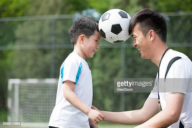 The boy and The coach face to face with football