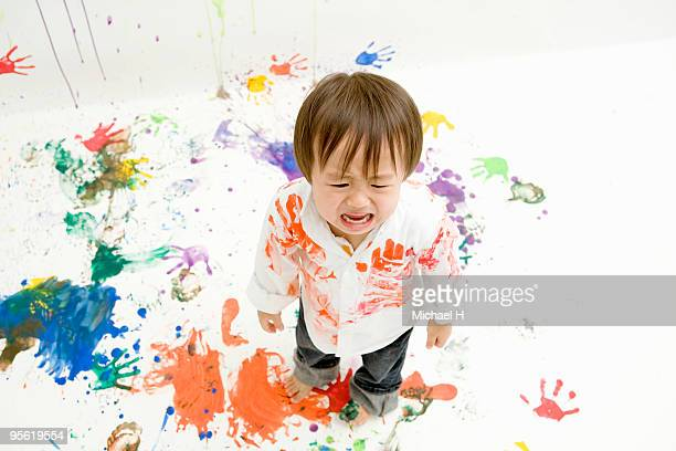 The boy covered with paint is crying