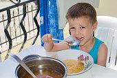 The boy eats soup on the terrace