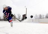 The boy plays hockey on a street skating rink.A boy on a skating rink plays hockey.