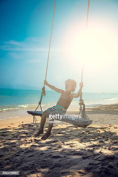 The boy sitting on swing on the beach