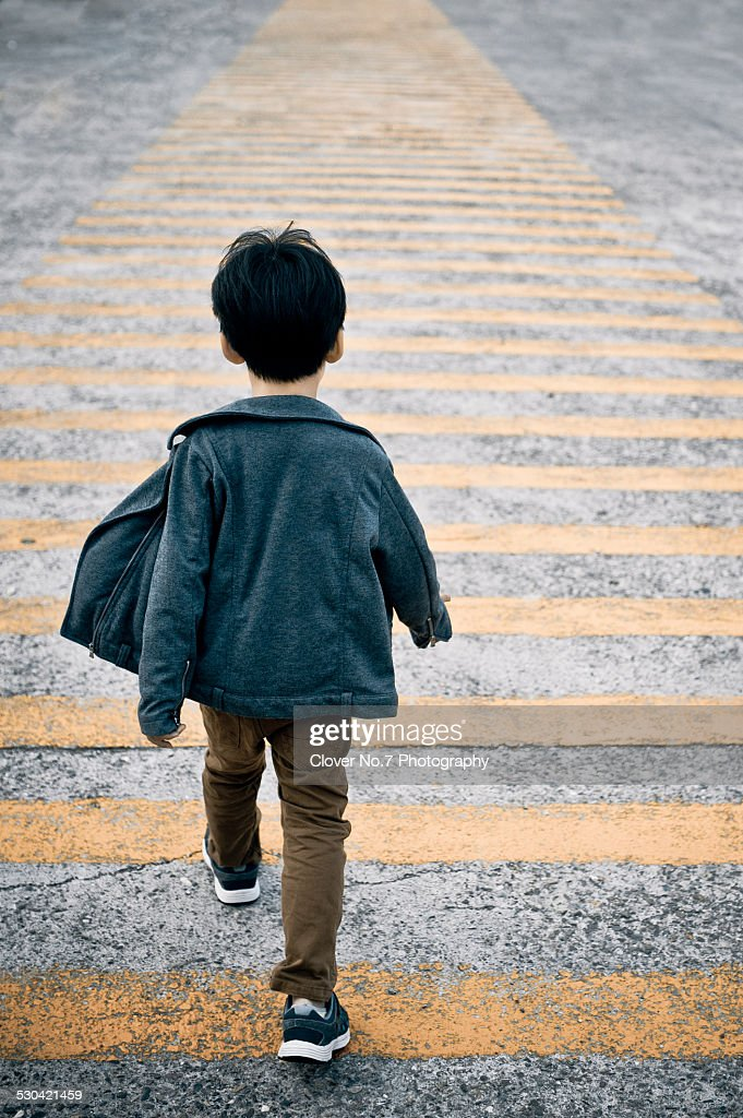 The boy walked zebra lines.