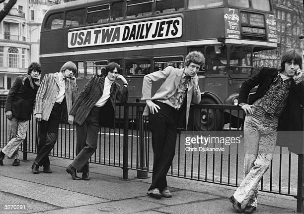 The boys from pop group Gentle Influence lean on a fence in a London street