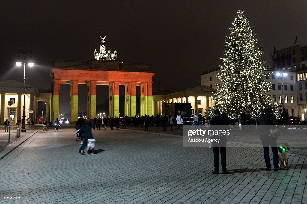 The Brandenburg Gate (Brandenburger Tor) is illuminated in black, red and gold, the colors of the German Flag to pay tribute to the victims of the attack on a Christmas market in Berlin, Germany on December 20, 2016. At least 12 people were killed and 48 others injured when a truck crashed into a crowded Christmas market in the German capital.