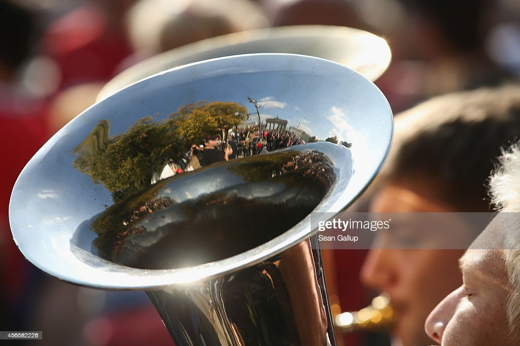 The Brandenburg Gate is reflected in the horn of a Bavarian brass band performing on German Unity Day (Tag der Deutschen Einheit) in Tiergarten Park on October 3, 2014 in Berlin, Germany. Germany is celebrating the 24th anniversary of the day when former West Germany and East Germany reunited into modern Germany in 1990 following the end of the Cold War. This year Germany will also celebrate the 25th anniversary of the fall of the Berlin Wall that heralded the collapse of communist authority in East Germany.