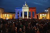 The Brandenburg Gate stands illuminated in the colors of the French flag as people arrive to lay candles and flowers at the gate of the adjacent...