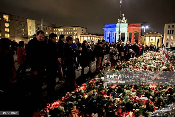 The Brandenburg Gate stands illuminated in the colors of the French flag as people lay candles and flowers at the gate of the nearby the French...