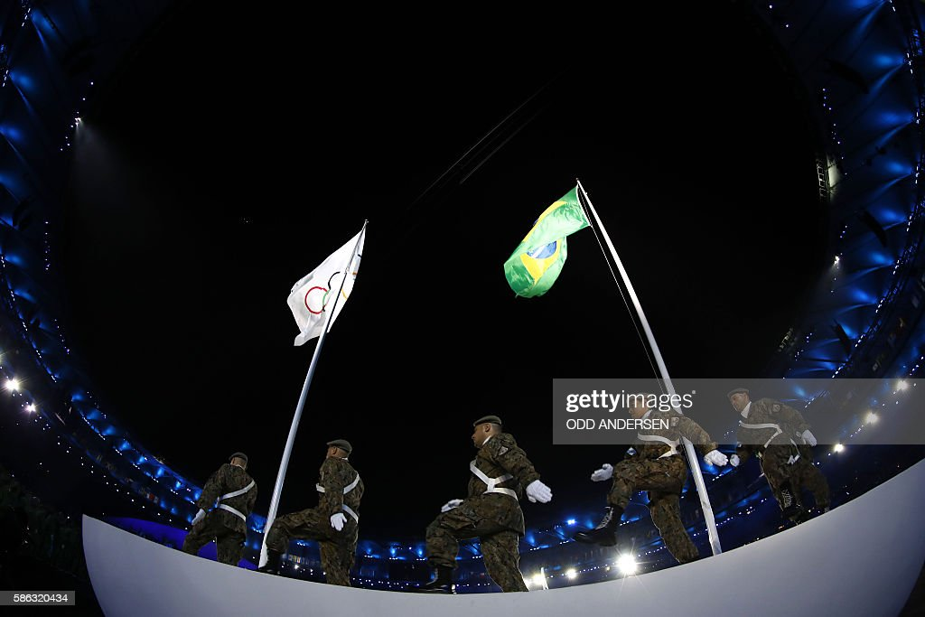 The Brazilian and Olympic flag are raised during the opening ceremony of the Rio 2016 Olympic Games at the Maracana stadium in Rio de Janeiro on...